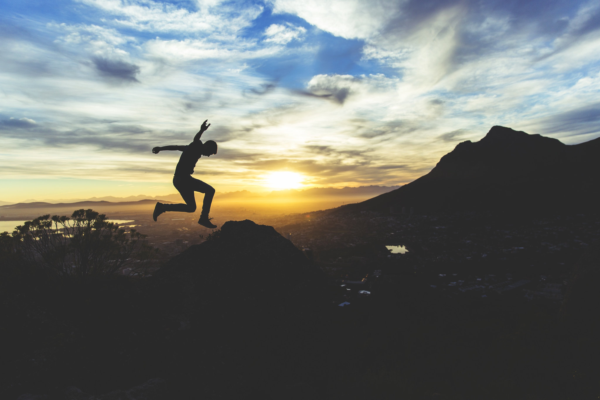 Man jumps near the peak of a mountain at sunrise.